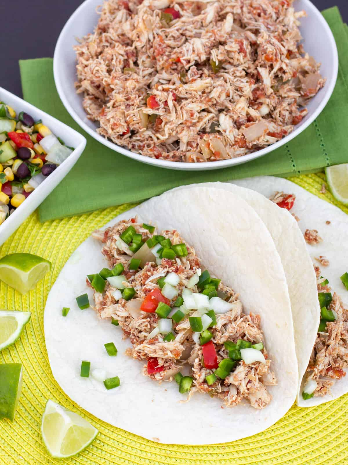 Slow cooker chicken carnitas topped with diced peppers and onions.