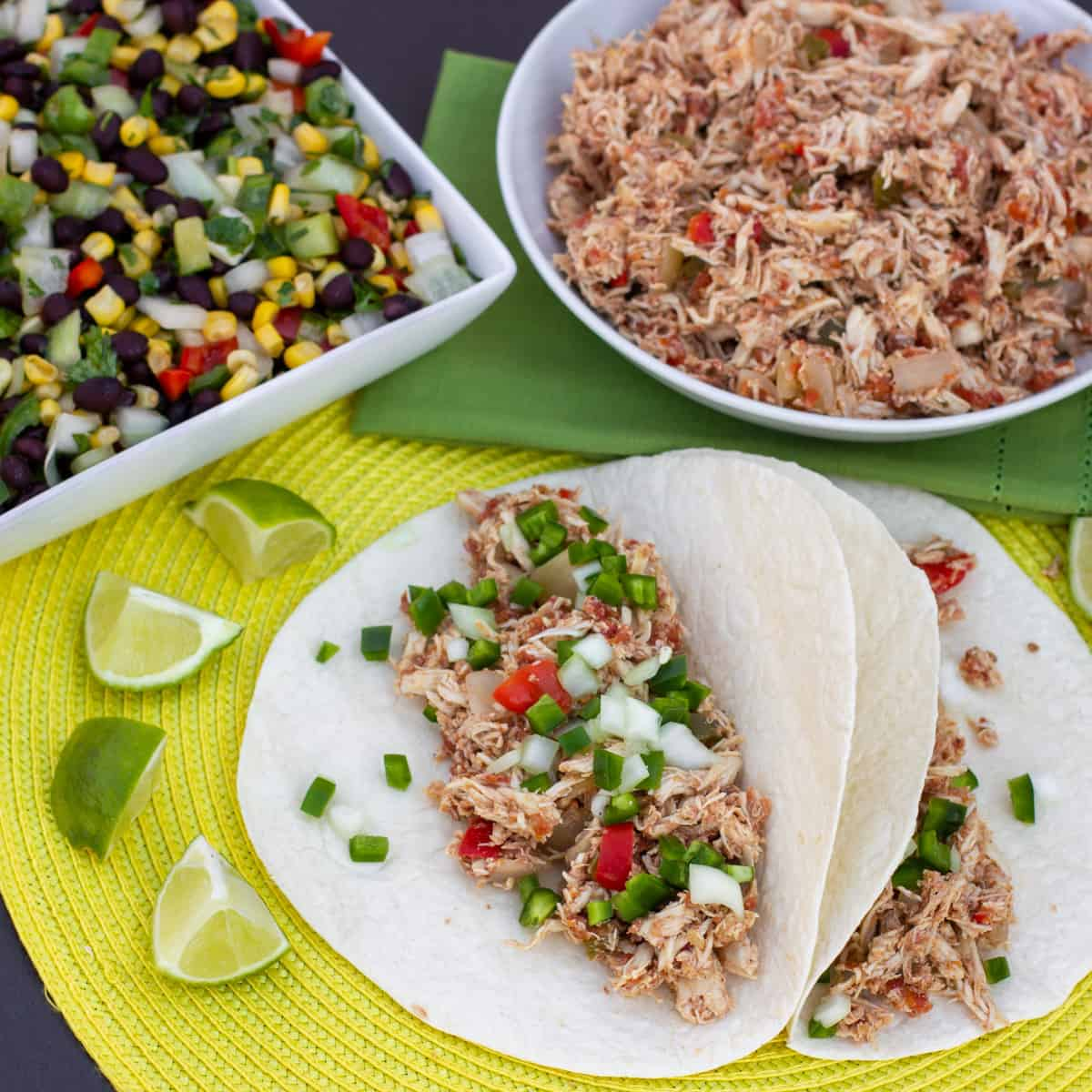 Overhead picture of chicken carnitas next to a bowl of black bean and corn salad