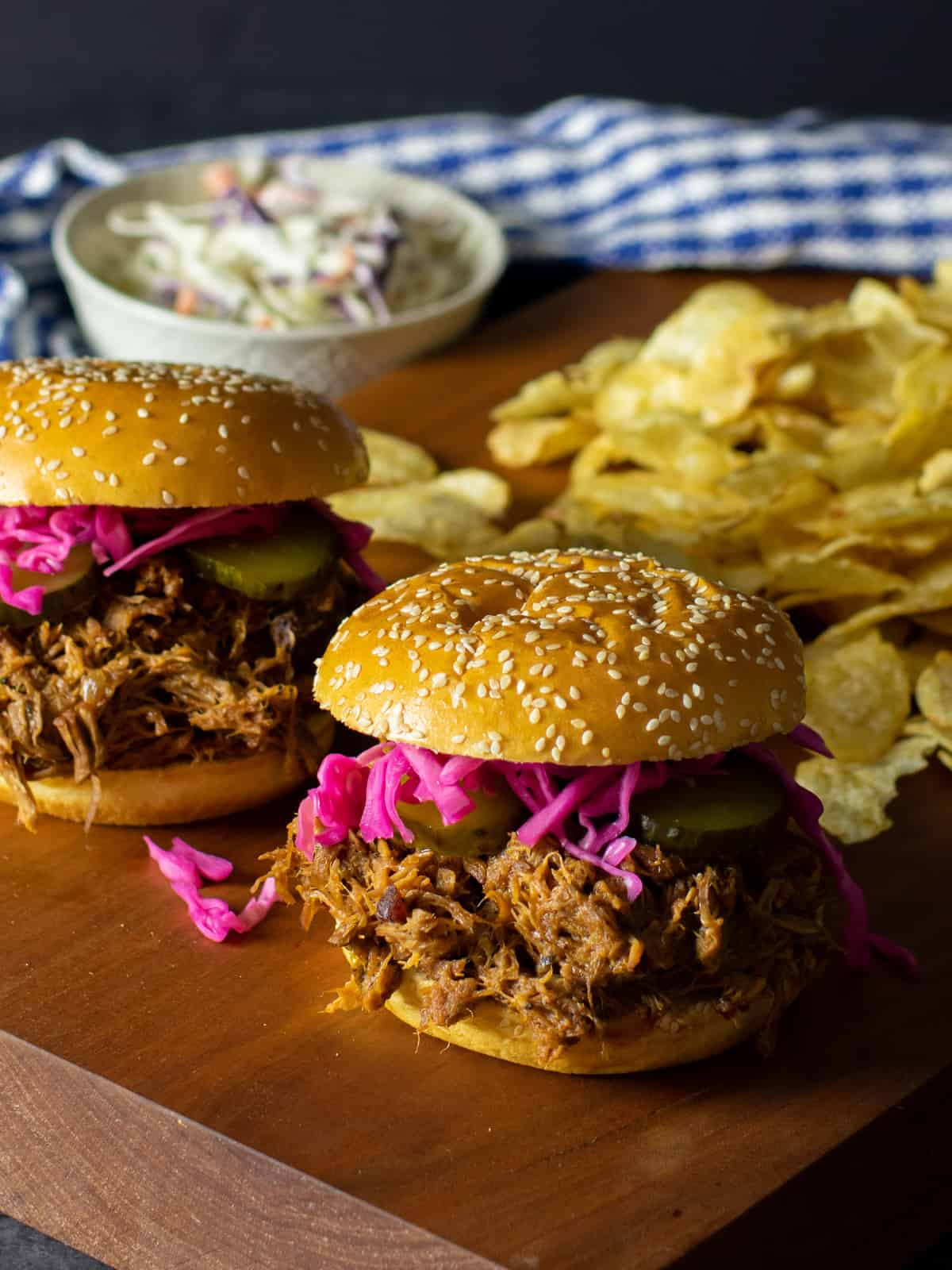 Pulled pork sandwiches on a cutting board with potato chips and cole slaw.